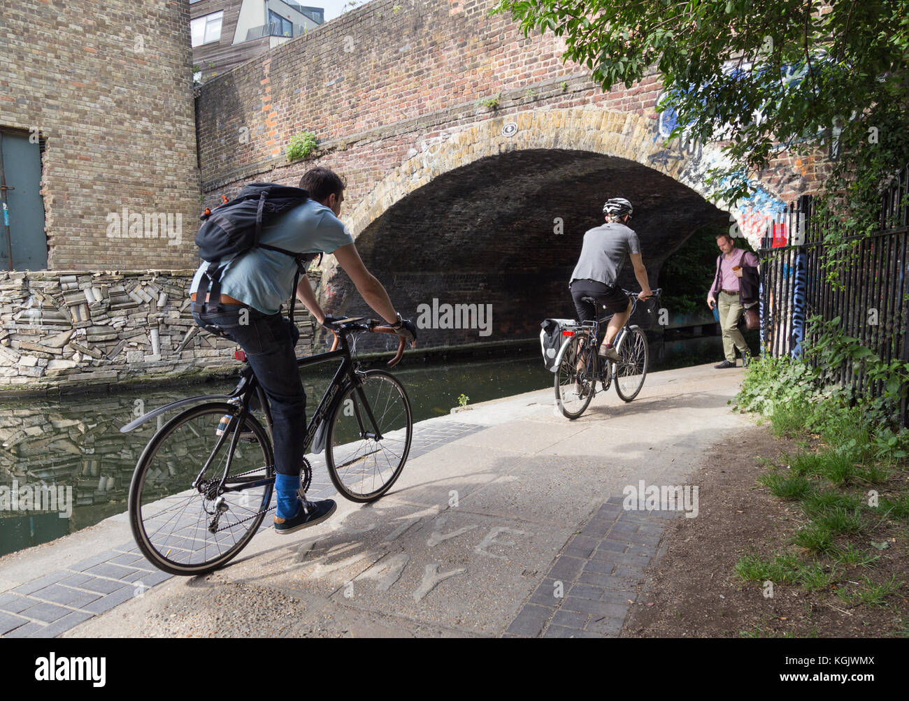 Cyclists cycling toward canal bridge arch with pedestrian walking in opposite direction on towpath by the Regent's - Stock Image