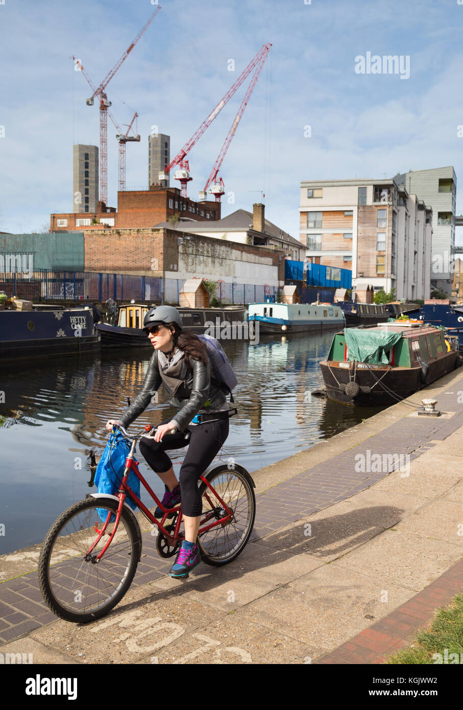 Young woman in a leather jacket cycles along towpath by Regent's Canal in east London, with construction cranes - Stock Image