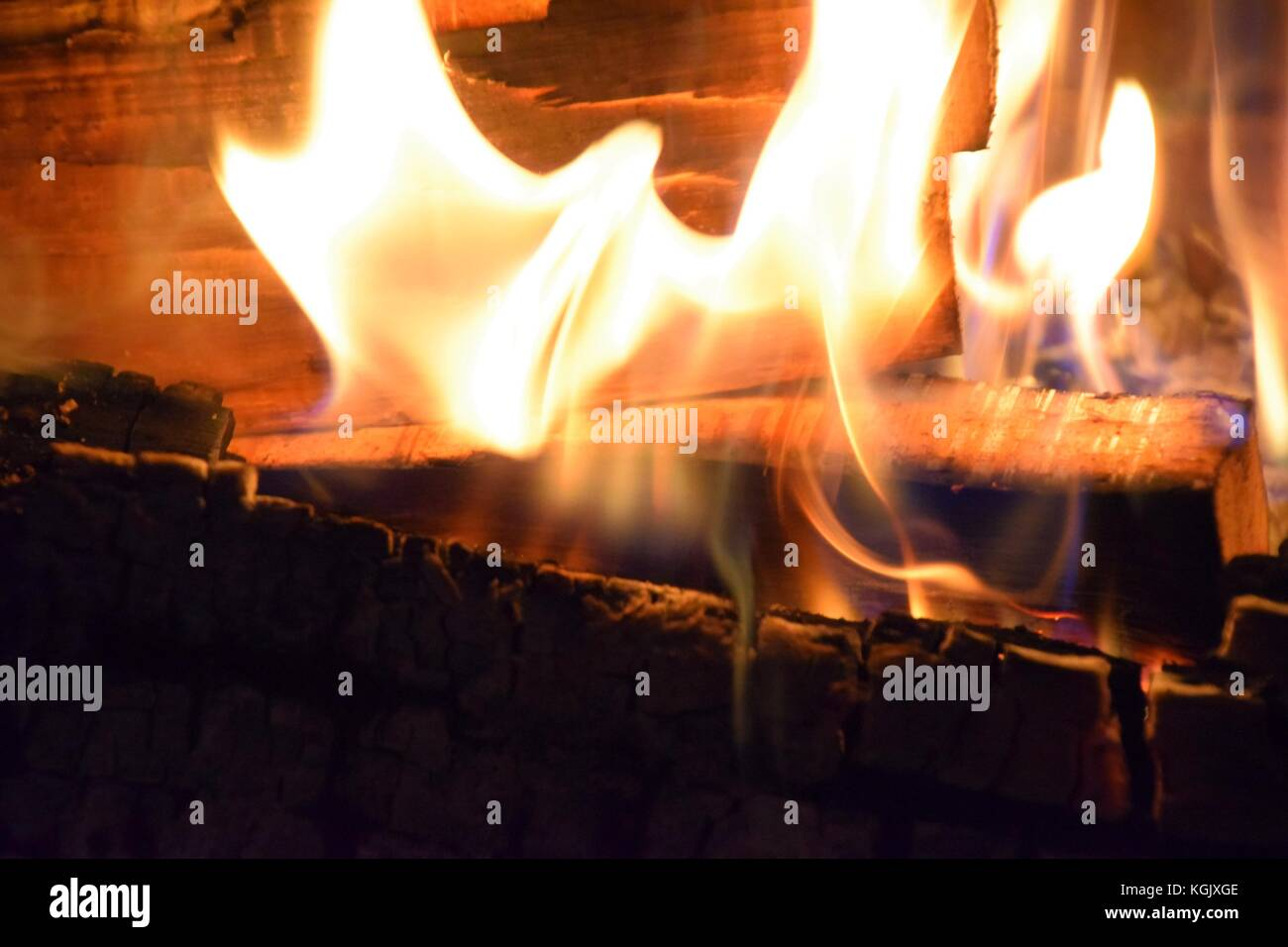 burning wood in a tiled stove with hot blazing flames - Stock Image