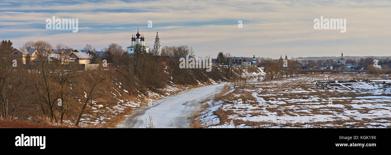 City landscape of Suzdal. River, ice-bound, In the flood plain lies snow. On the slope of the hill, the snow melted Stock Photo