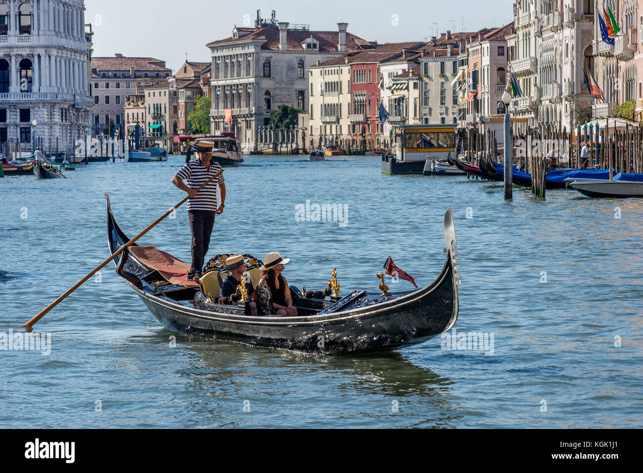 Honeymooners crossing the Grand Canal on a gondola, Venice, Italy - Stock Image