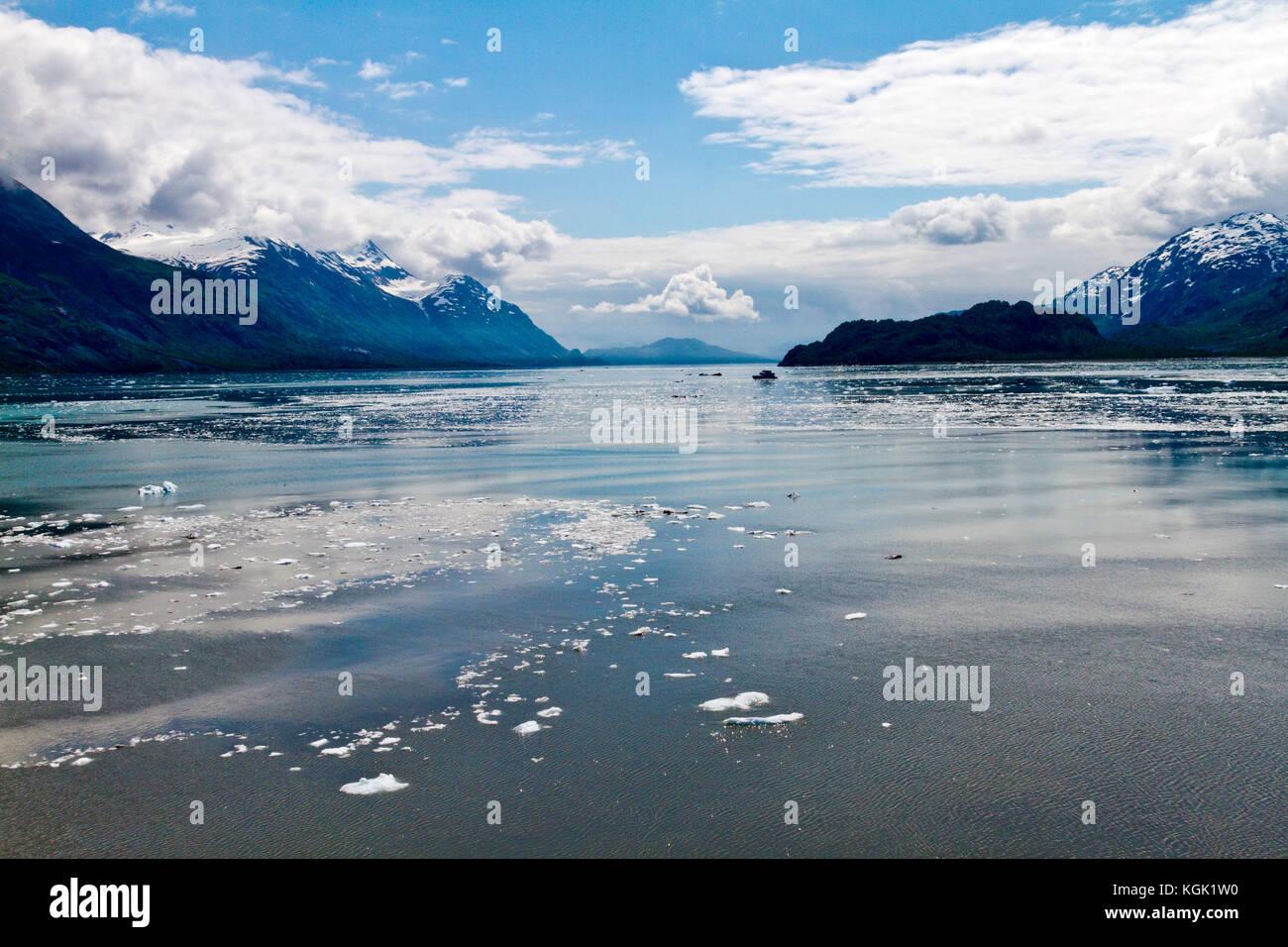 A small boat. alone and dwarfed, traveling on Glacier Bay, Alaska. - Stock Image
