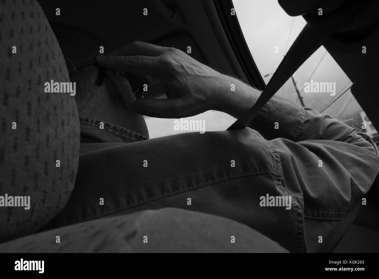 A man sits in his car, placing his hand next to his head in a pondering manner, contemplating on his thoughts. But - Stock Image