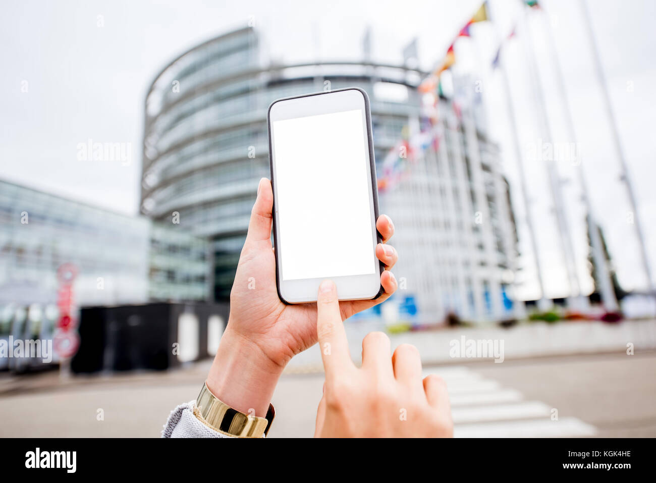 Holding phone on the European parliament building background - Stock Image