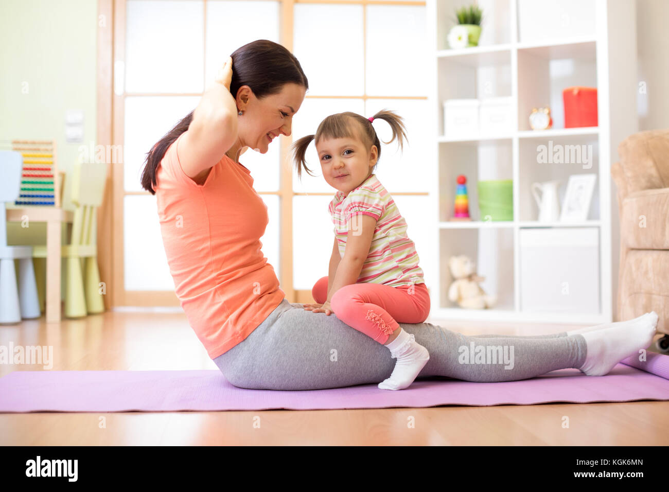 Mother and child daughter are engaged in fitness, yoga, exercise at home. Kid and woman swing press on stomach. - Stock Image