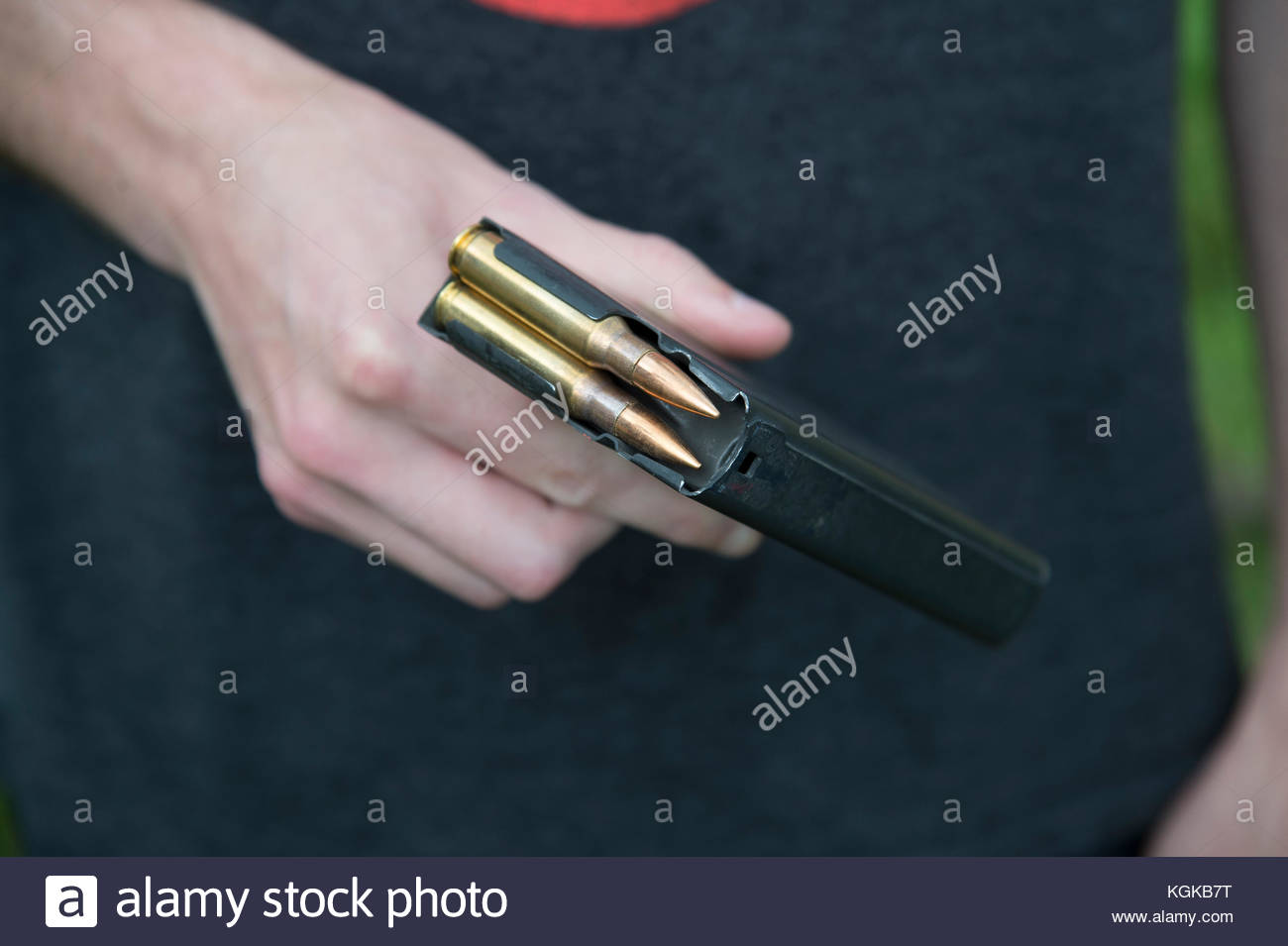 A young man holds a magazine of rifle bullets. - Stock Image