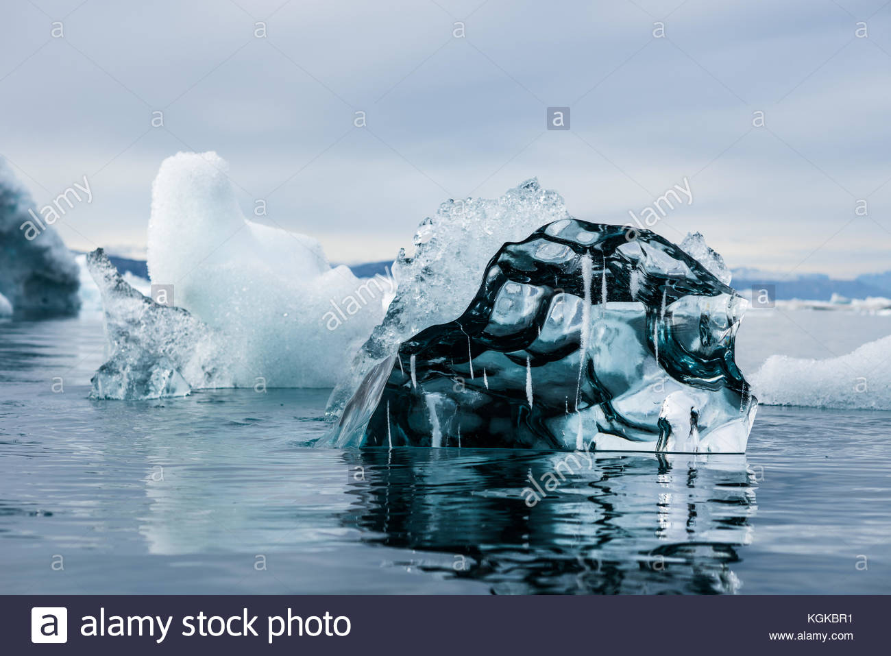 A transparent iceberg floating in the water. - Stock Image