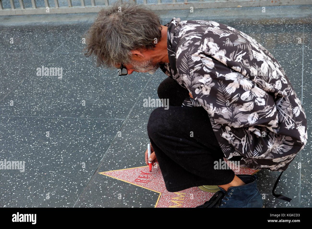A homeless man signs his name on a Hollywood Walk of Fame Star on Hollywood Boulevard in Los Angeles, California Stock Photo