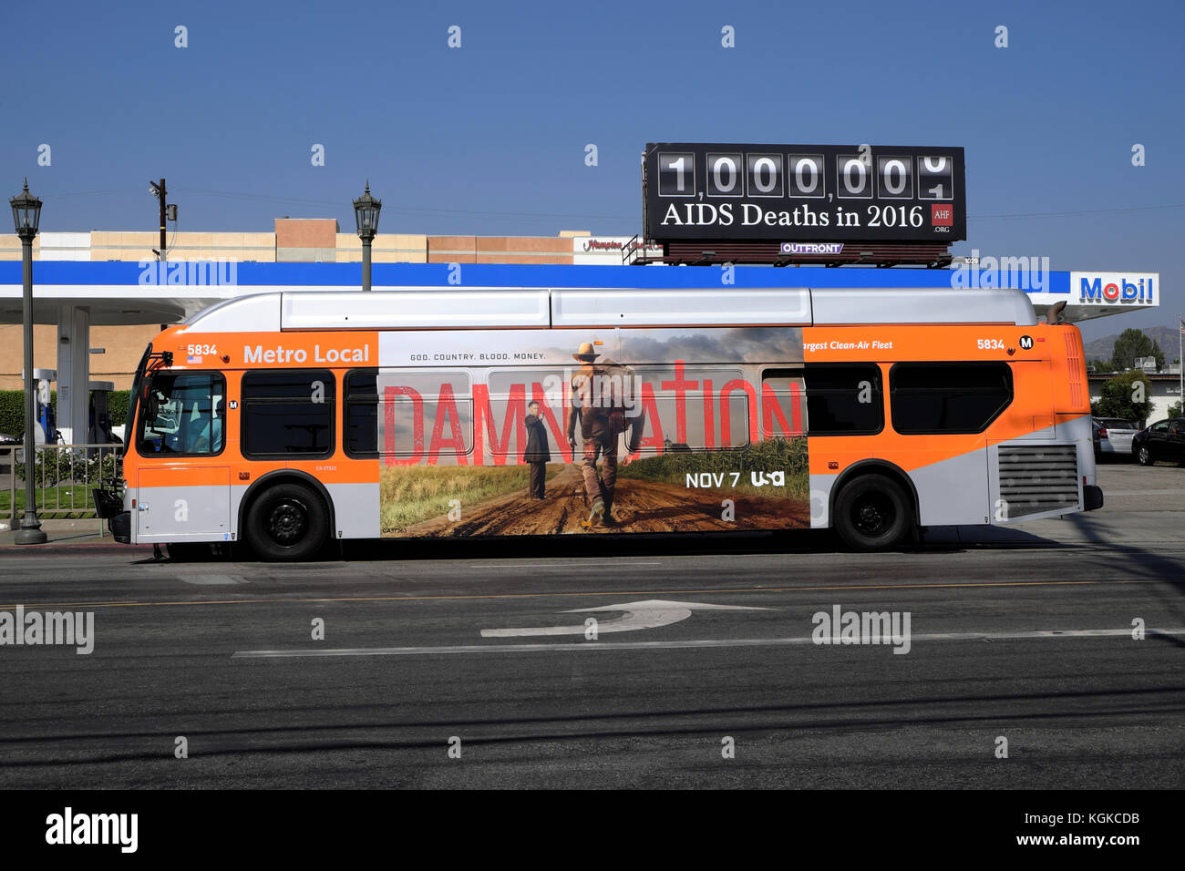 An advertisement for the movie DAMNATION on the side of an orange metro bus & Aids Deaths Counter billboard - Stock Image
