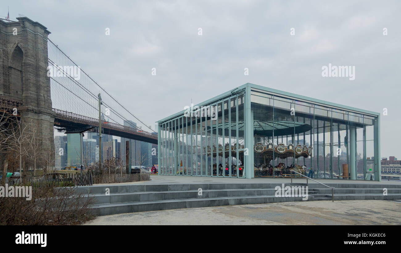 Jane's Carousel in Brooklyn Bridge Park with the Brooklyn Bridge in the background. - Stock Image