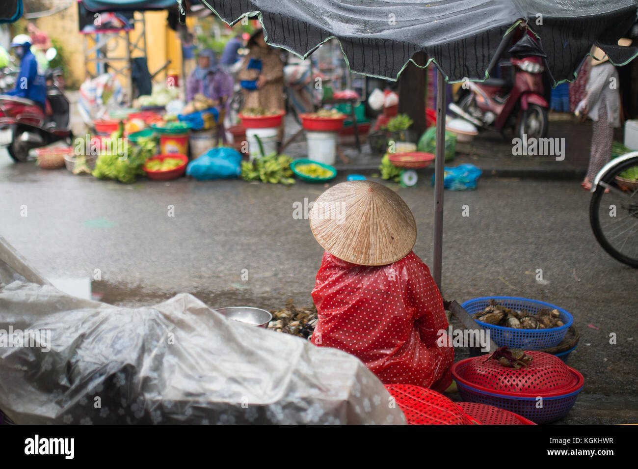-Selective focus- Unidentified woman with typical vietnamese conical hats sell fresh vegetables on a street market in Hoi An, Vietnam Stock Photo