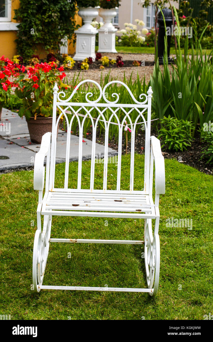 Single Old Fashioned Ornate White Wrought Iron Garden Rocking Chair In A  Lush Green Garden