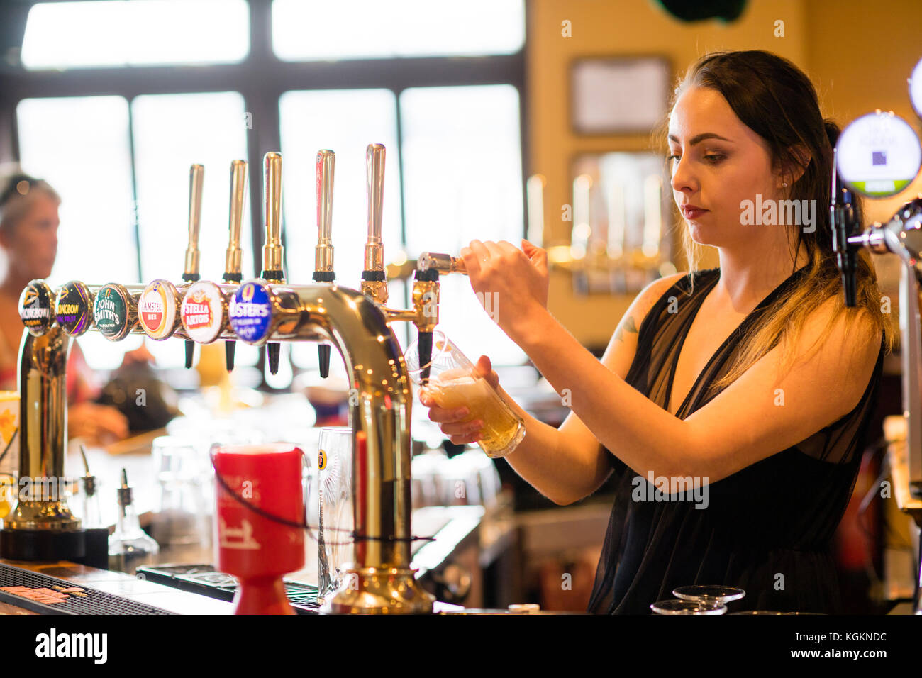 A barmaid bar worker pouring a pint of draught lager beer in a bar pub club UK - Stock Image