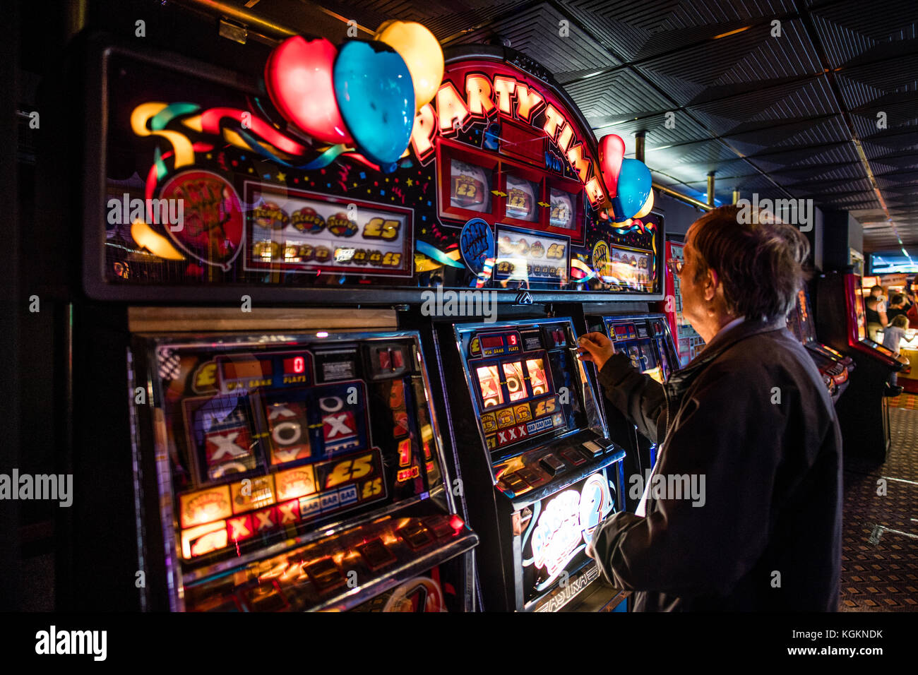 A Man Playing On A Party Time One Armed Bandit Fruit Machine Or Stock Photo Alamy