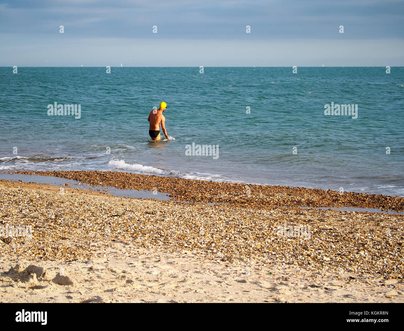 A man wearing swimming trunks and swim hat wades into the solent in an Autmn day - Stock Image