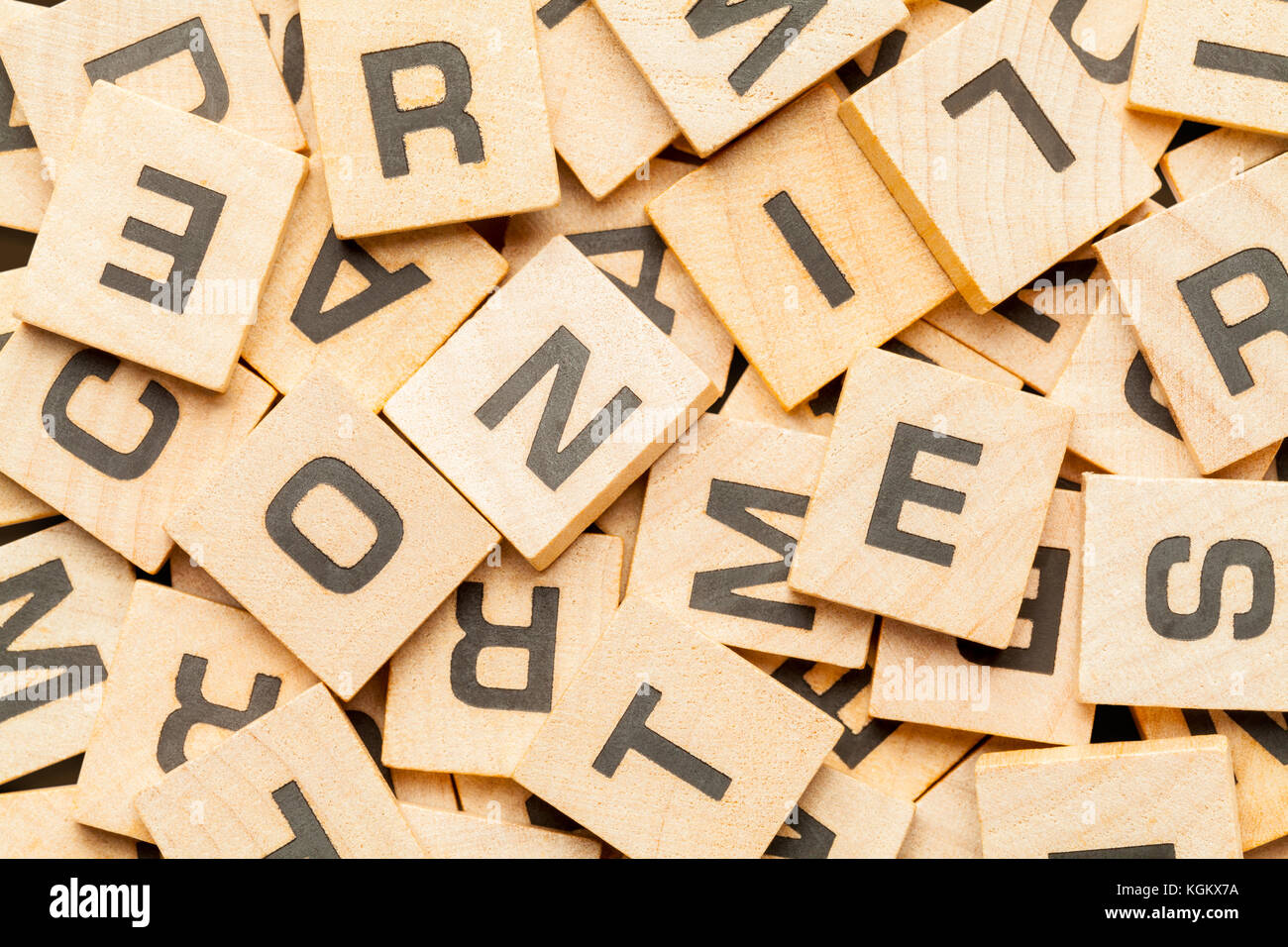 Pile of Wood Letter Game Tiles Background. Stock Photo