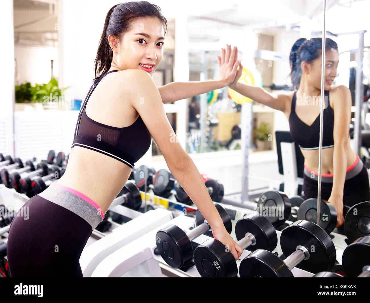 young asian woman looking at camera smiling while working out in fitness center. - Stock Image