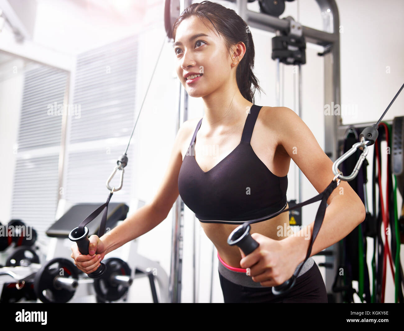 young asian woman working out in gym using exercising equipment. - Stock Image