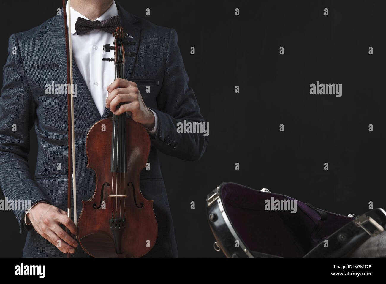 Midsection of man holding violin while standing by case against black background - Stock Image