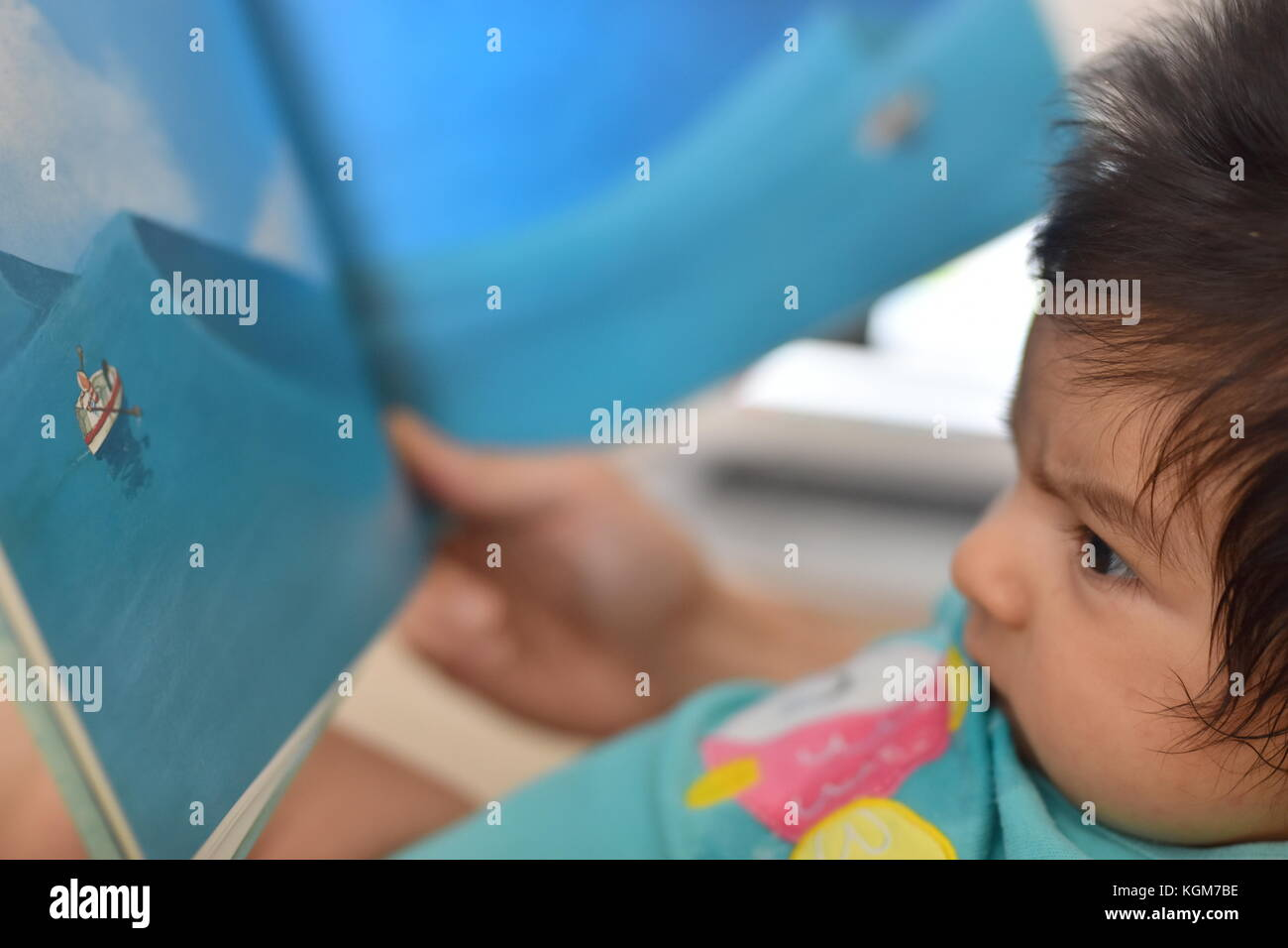 Newborn baby attentively reading children's book with illustrations - Stock Image
