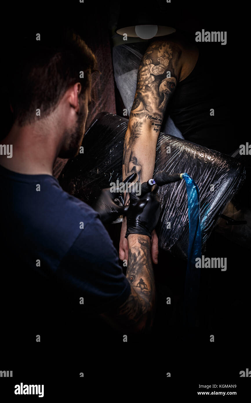 Master tattoo draws the black paint on the clients tattoo. - Stock Image