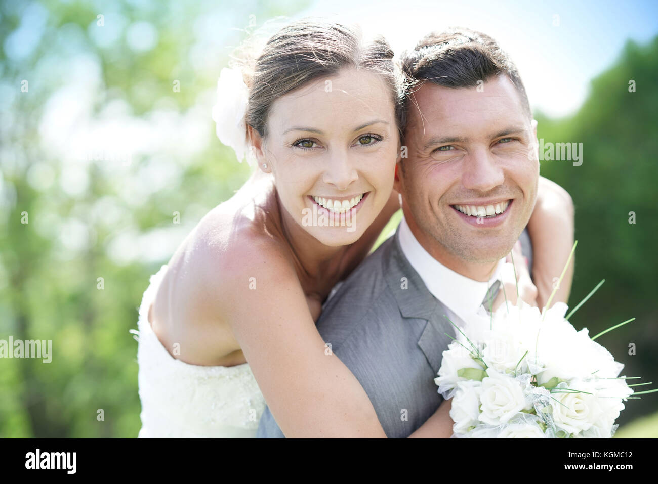 Groom giving piggyback ride to bride in countryside - Stock Image