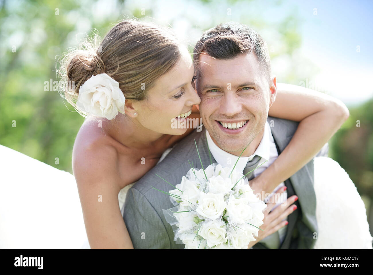 Groom giving piggyback ride to bride in countryside Stock Photo