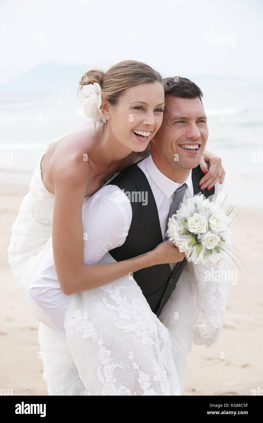 Groom giving piggyback ride to bride on the beach - Stock Image