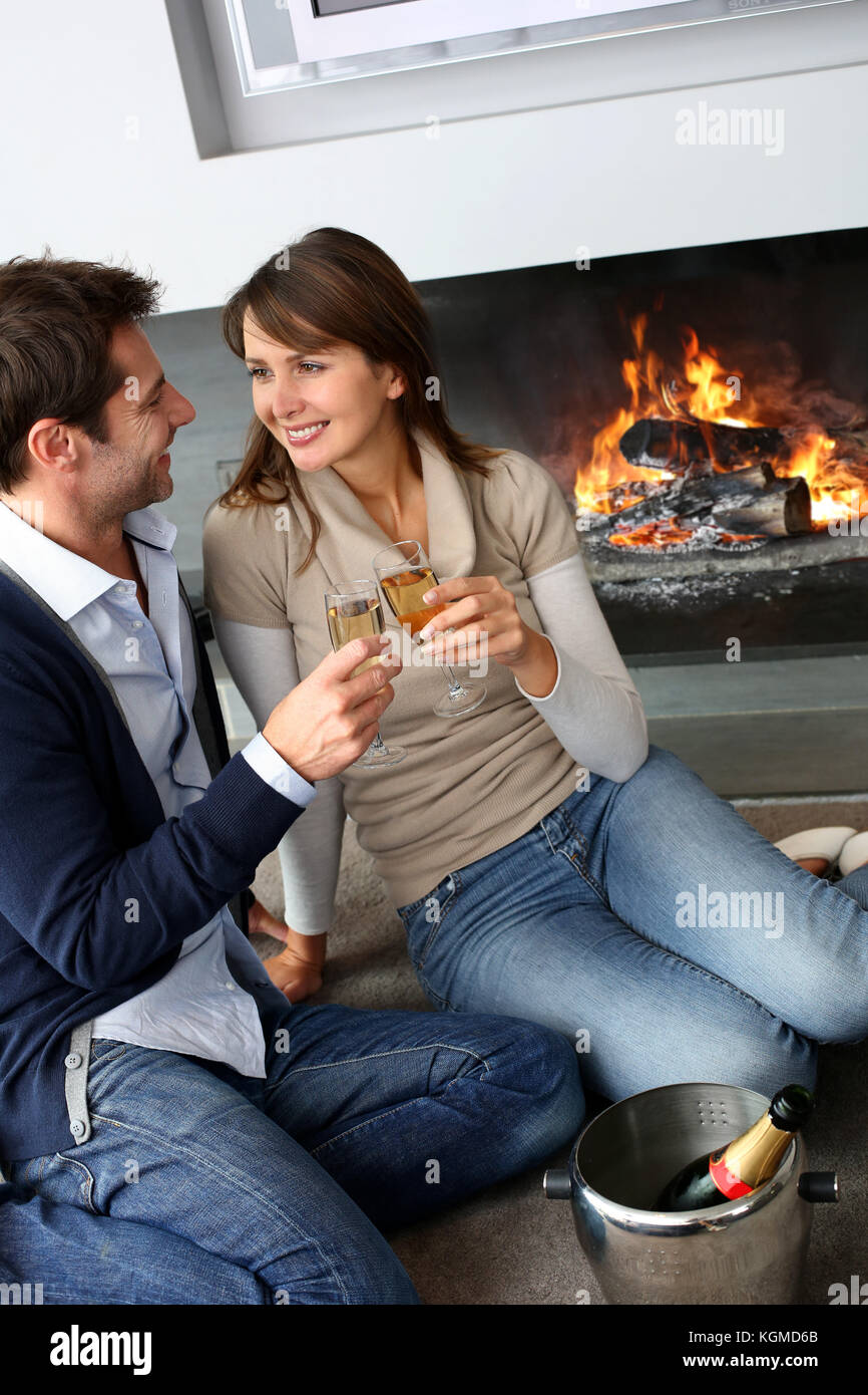 Cheerful couple drinking champaign by fireplace - Stock Image
