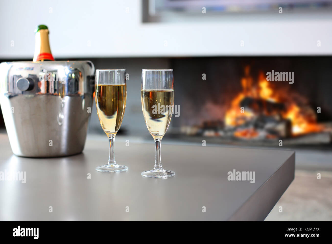 Closeup of champaign glasses set by fireplace - Stock Image