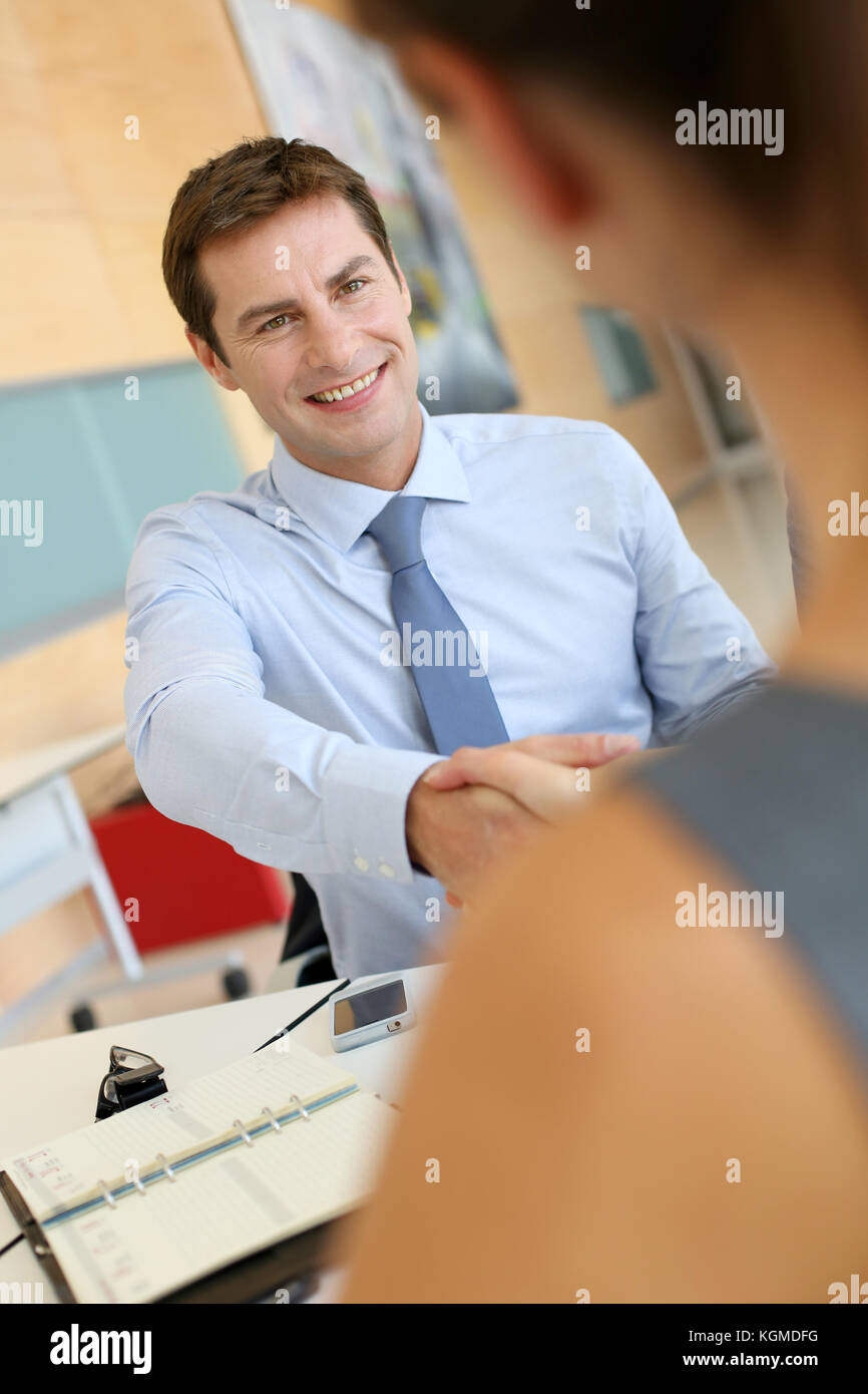 Business associates shaking hands in office - Stock Image