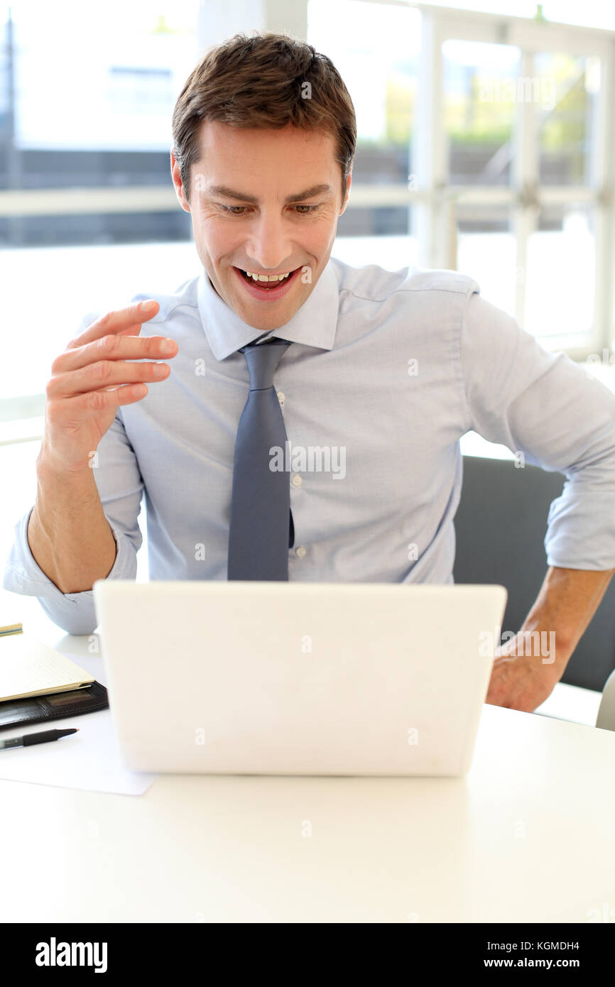 Businessman in front of laptop reading good news - Stock Image
