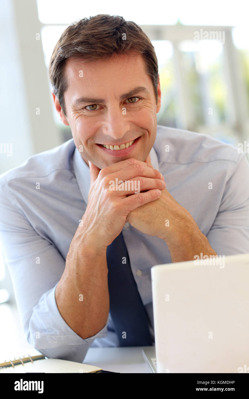 Happy businessman sitting in office - Stock Image