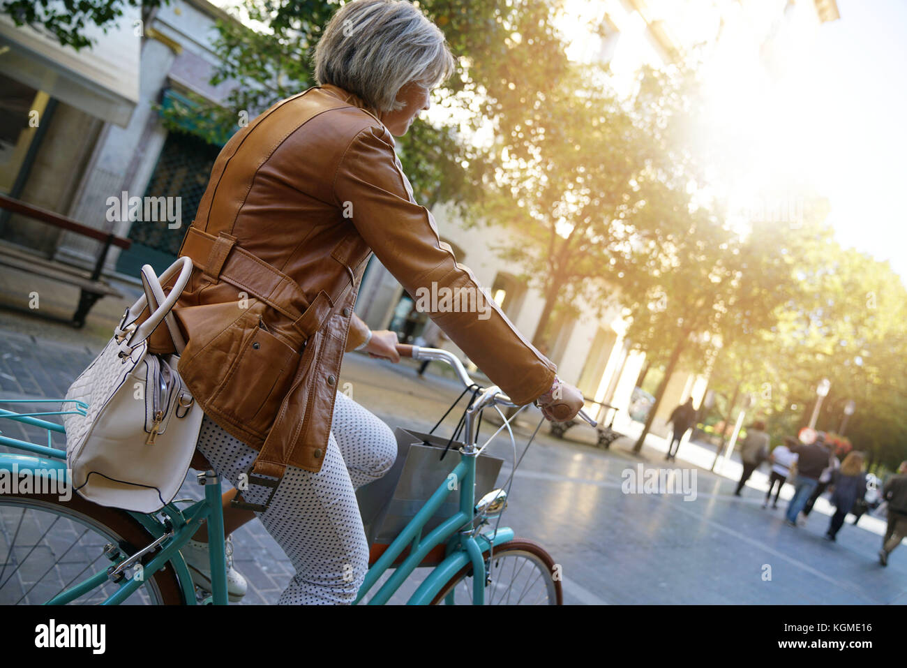 Senior woman riding city bike in town - Stock Image