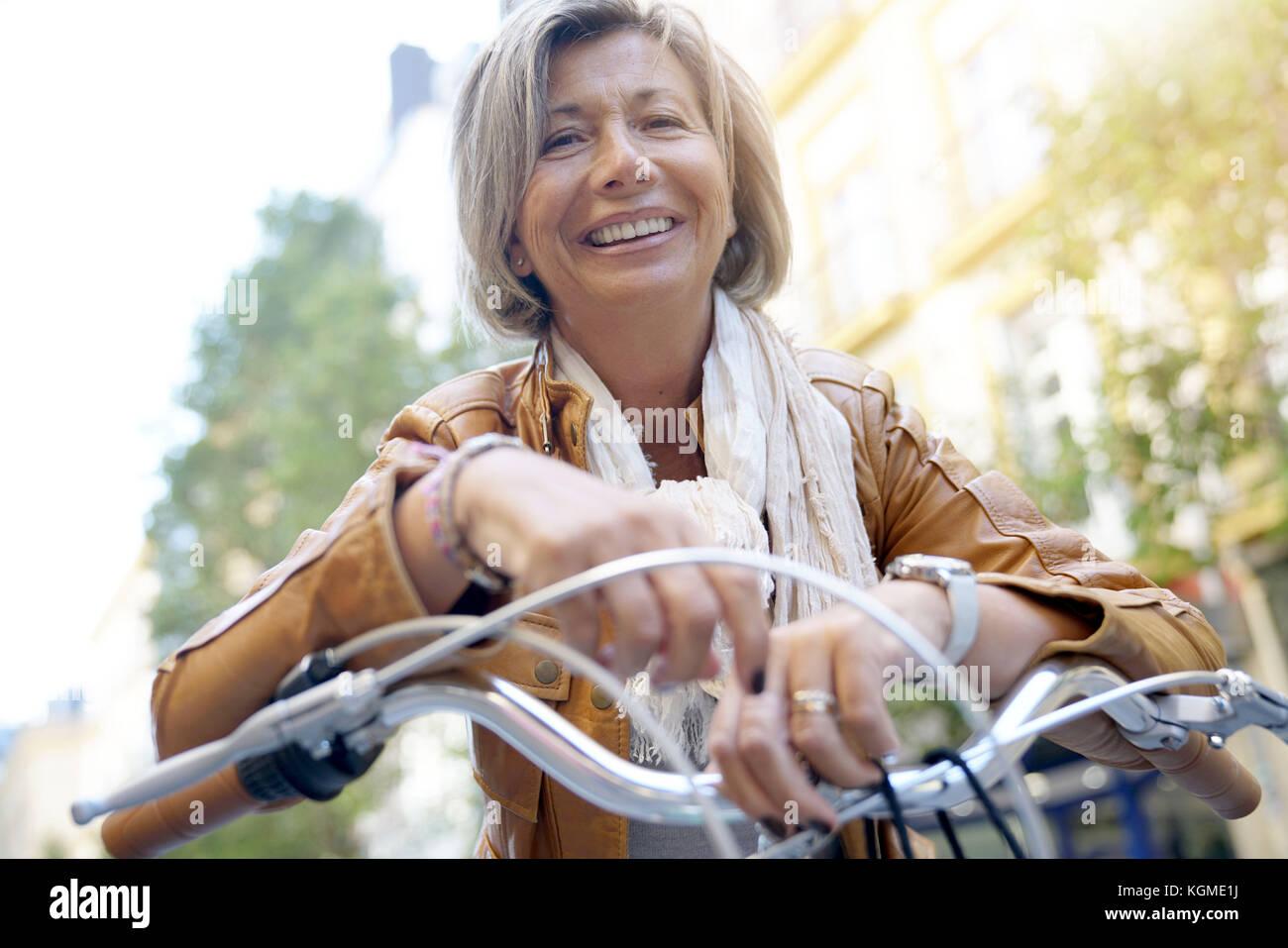 Portrait of senior woman riding city bike - Stock Image