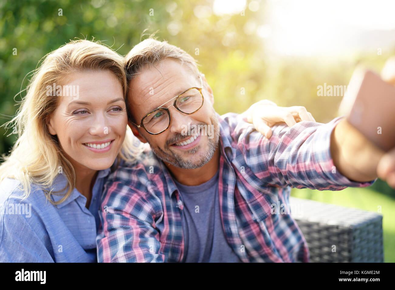 Portrait of cheerful mature couple taking selfie picture - Stock Image