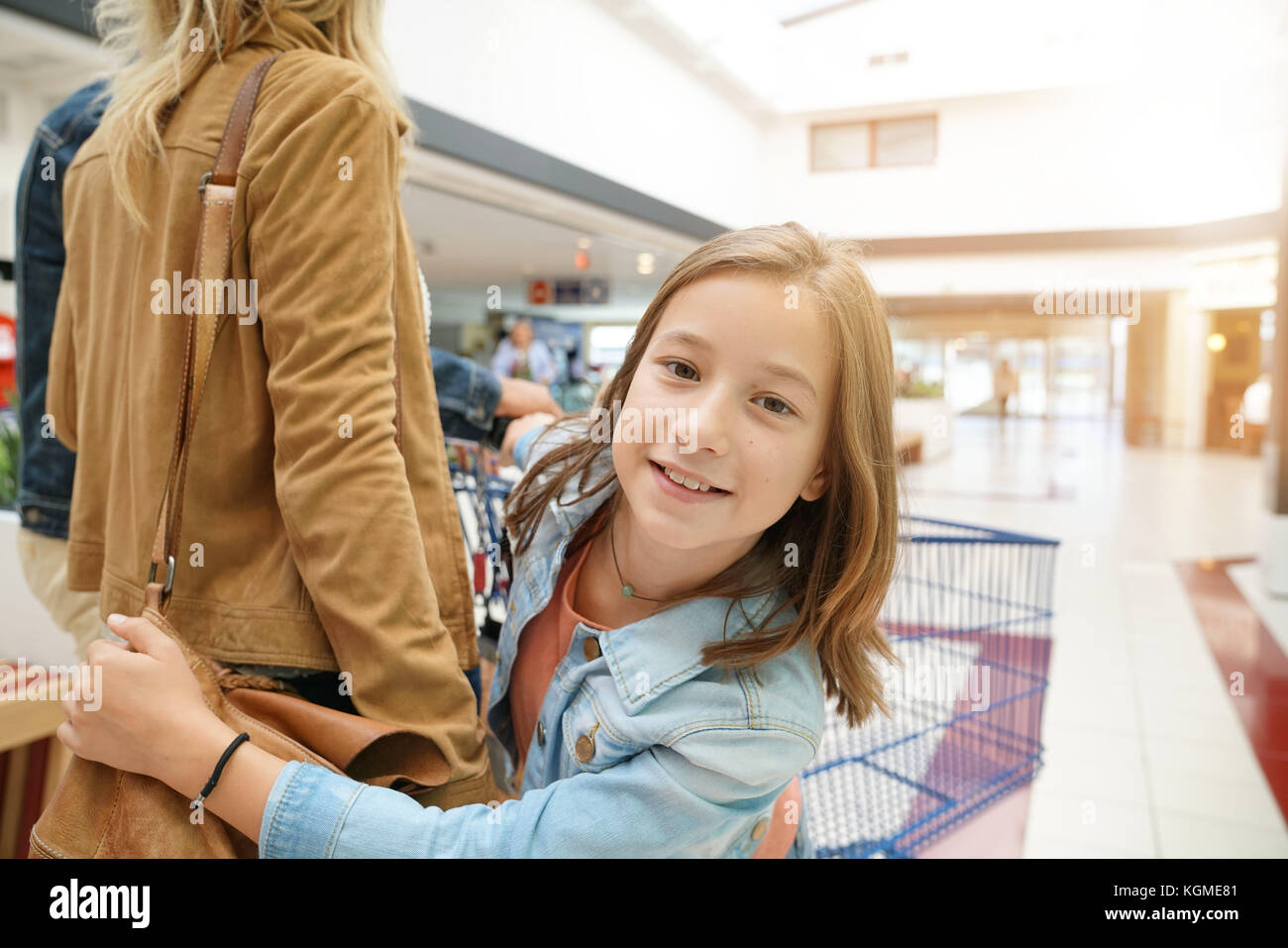 Portrait of young girl on shopping day with parents - Stock Image