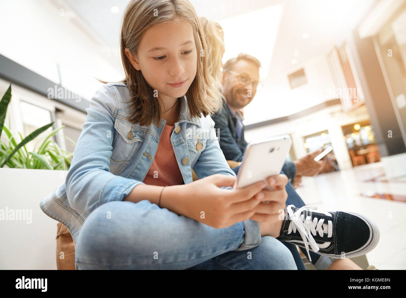 Young girl sitting on bench using smartphone, shopping day - Stock Image