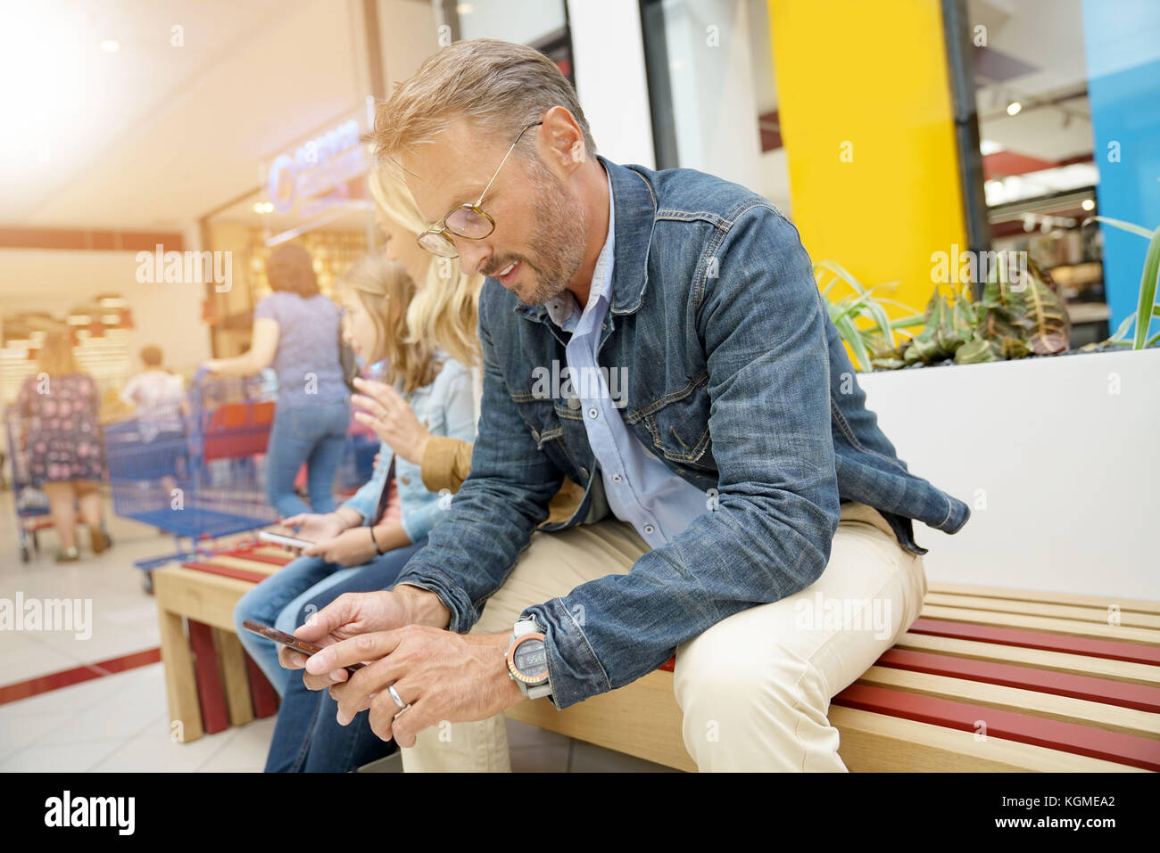 Man sitting on public bench in shopping mall - Stock Image