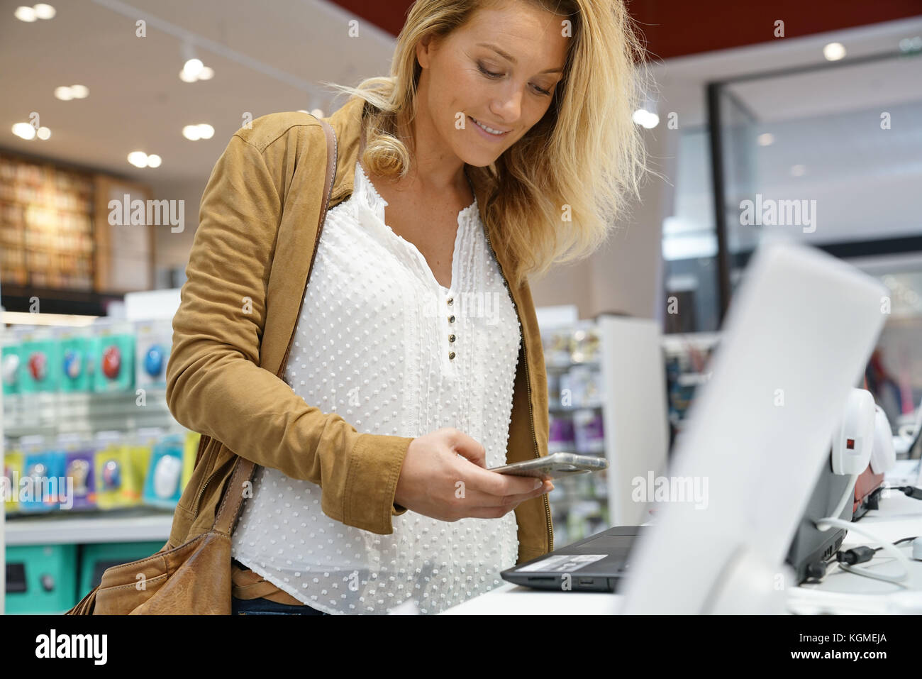 Woman in multimedia store looking at smartphones - Stock Image