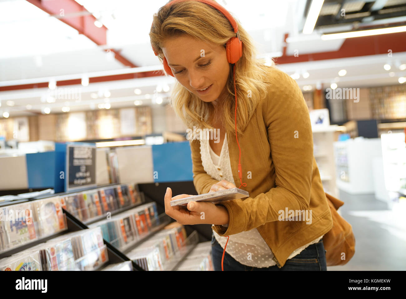 Woman in multimedia store testing new music discs - Stock Image