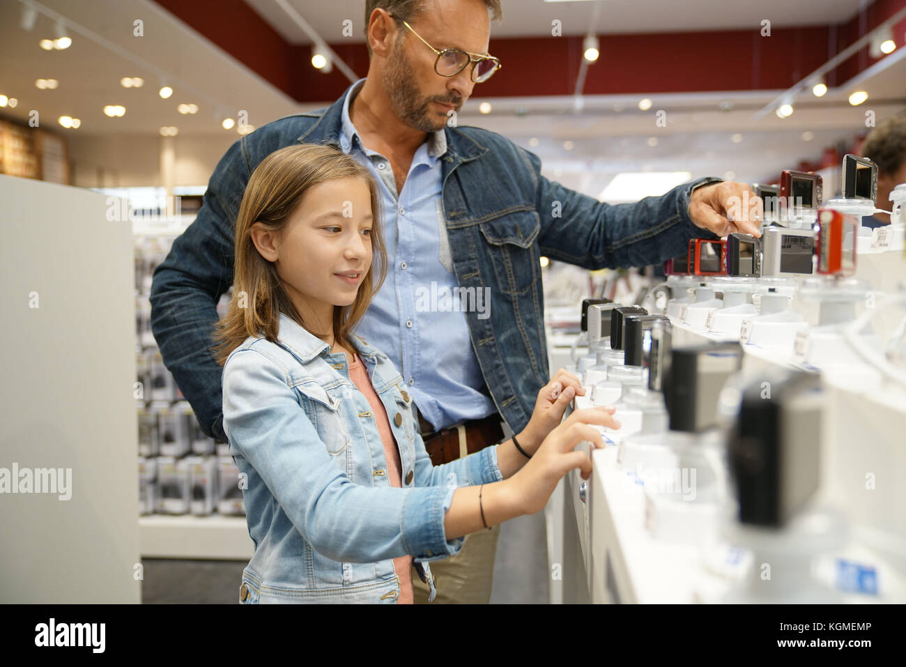 Man with kid looking at compact cameras in multimedia store - Stock Image