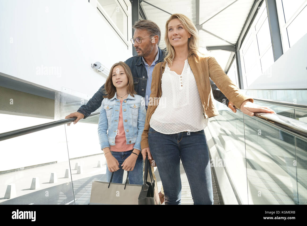Family going down escalator of shopping mall - Stock Image