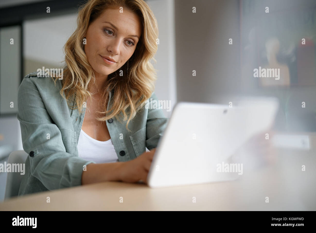 Woman sitting at home websufing on internet with digital tablet - Stock Image