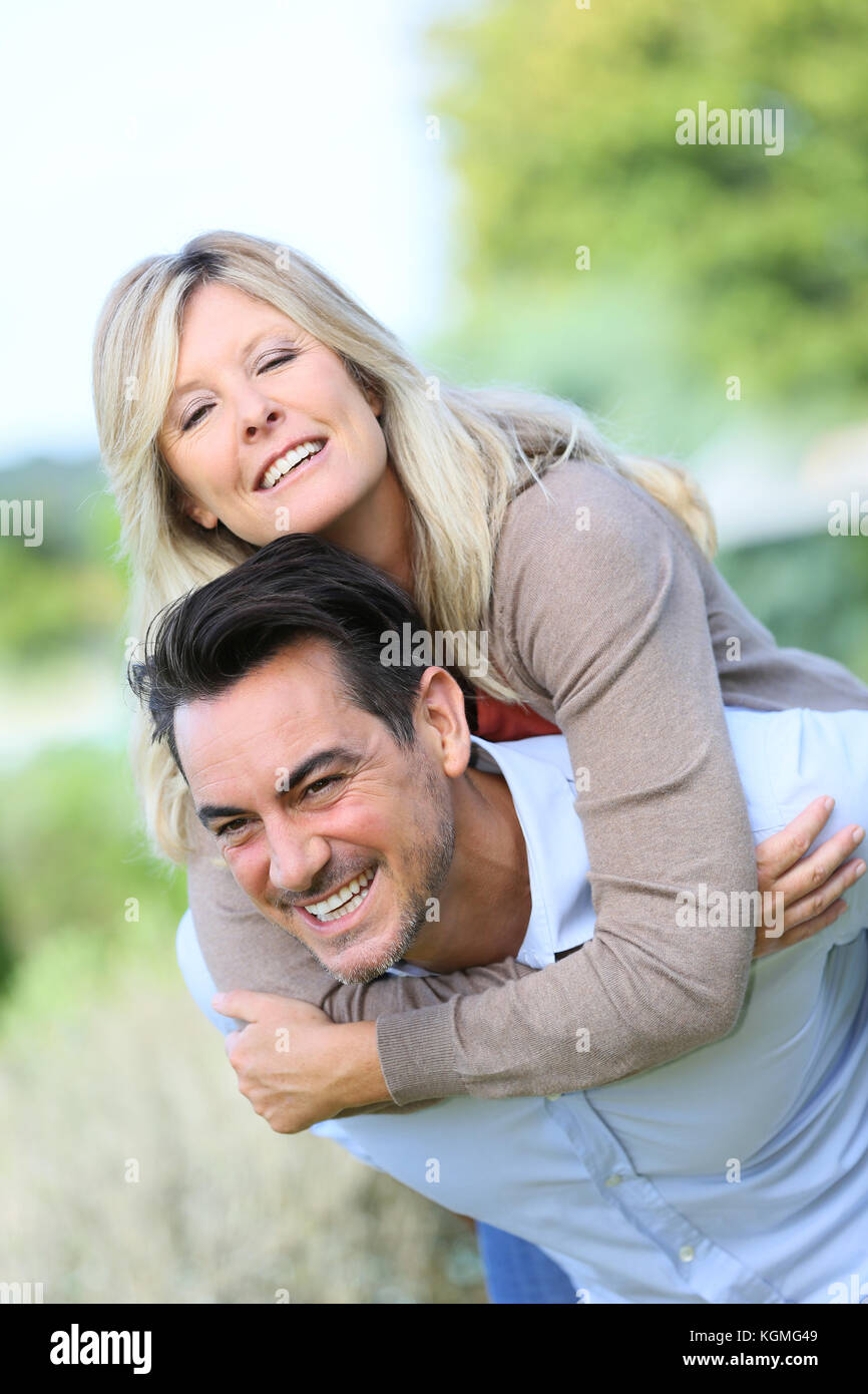 Cheerful mature man giving piggyback ride to woman - Stock Image