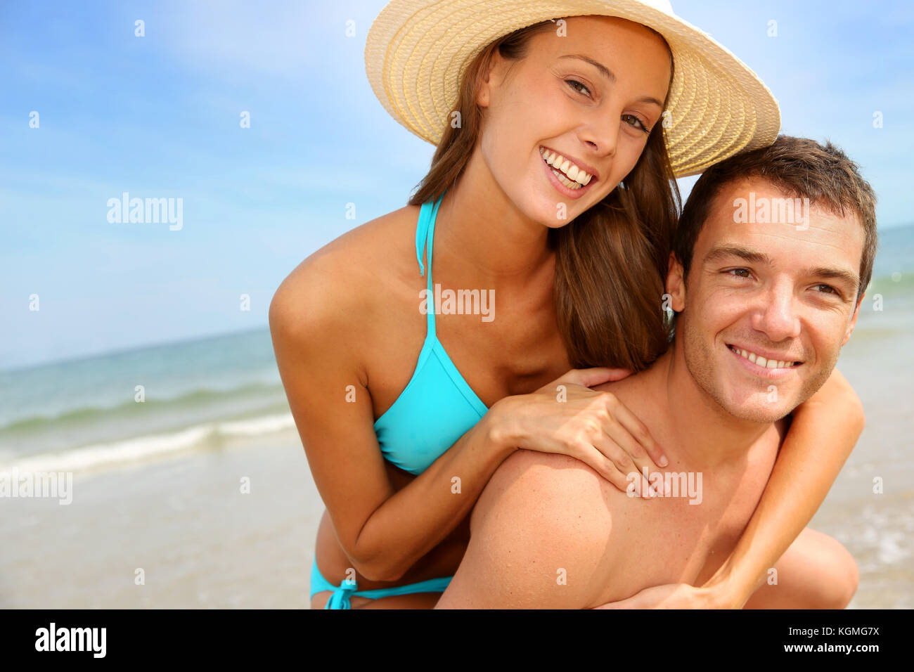 Man giving piggyback ride to girlfriend by the ocean - Stock Image