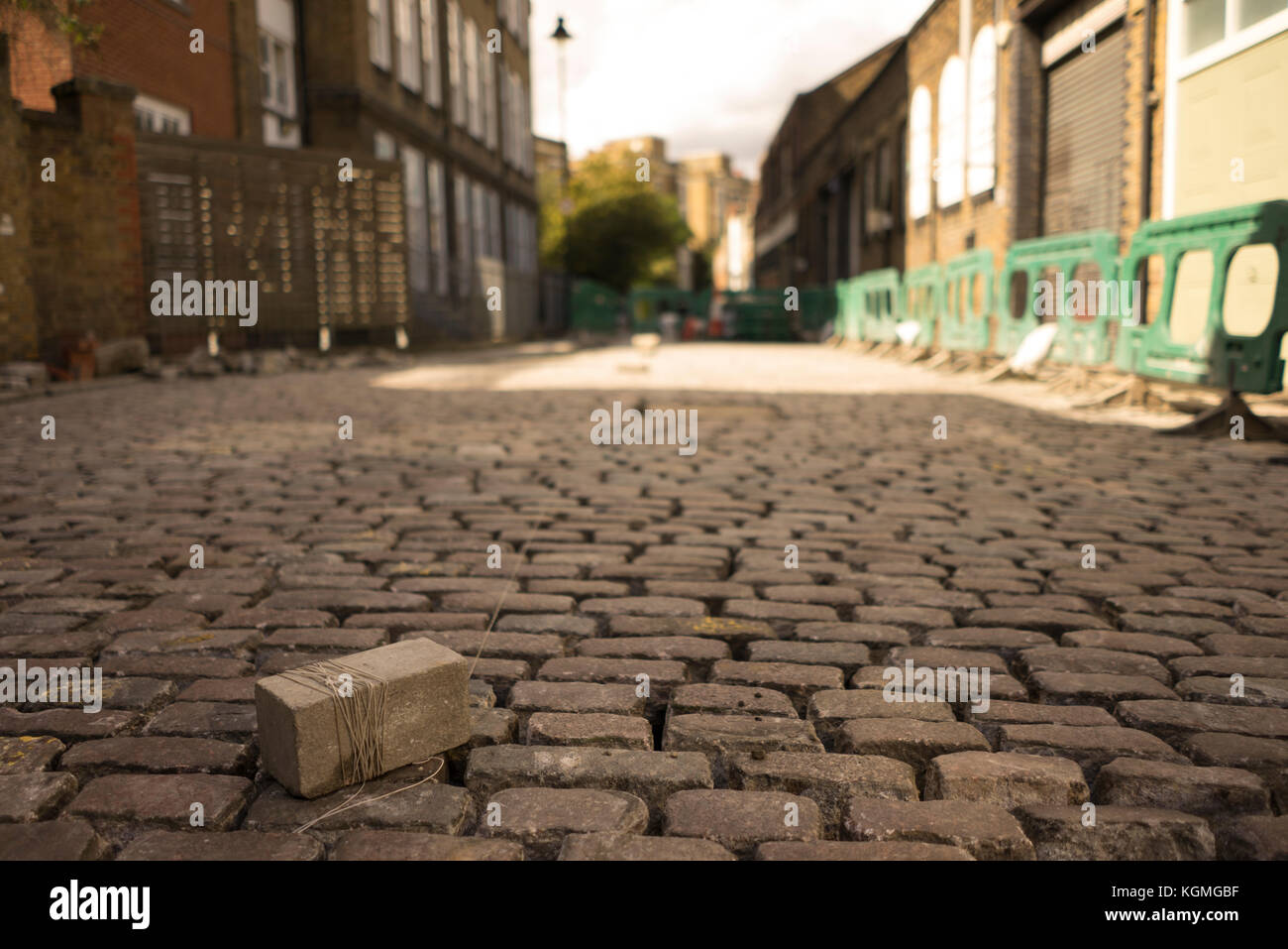 Repairing and refurbishing a cobbled street in Camden Town in North London tp conserve the Victorian industrial - Stock Image