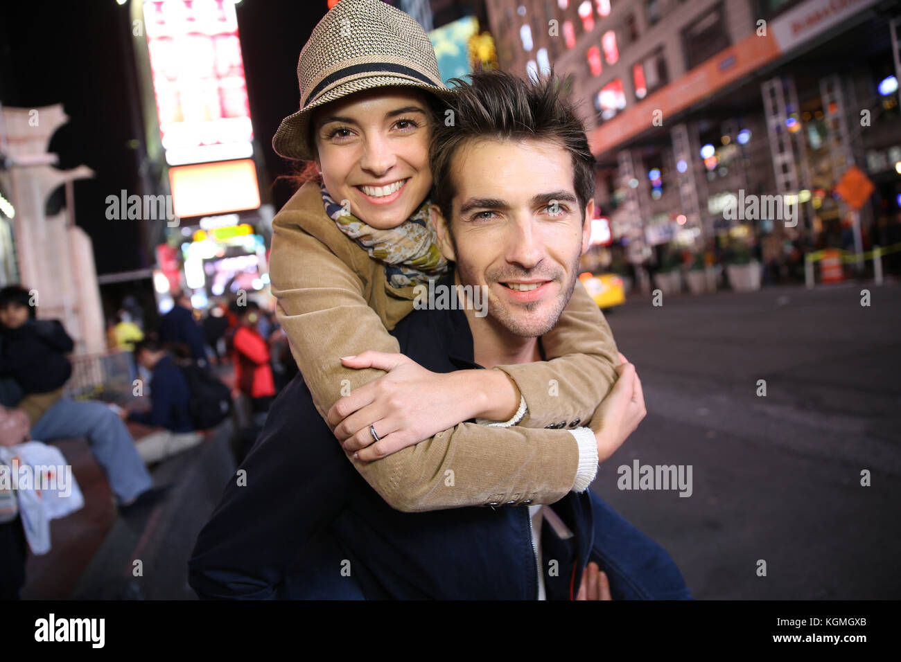 Couple standing in Time Square quarter by night - Stock Image