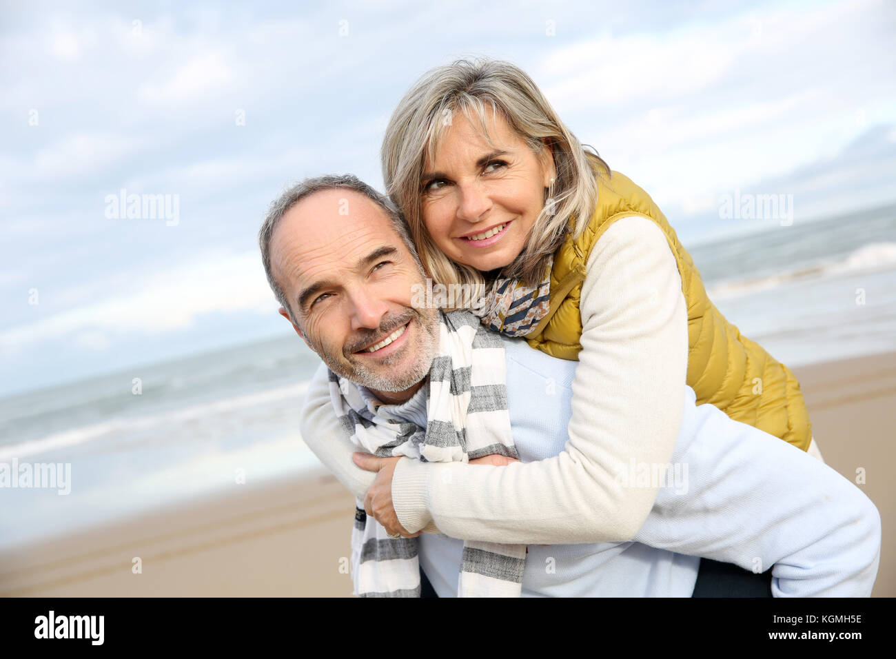 Senior man giving piggyback ride to wife - Stock Image