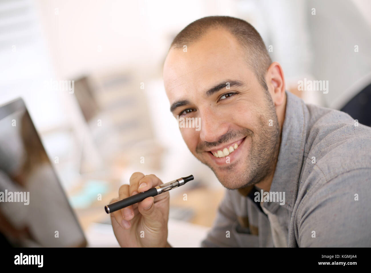 Portrait of cheerful guy smoking with e-cigarette - Stock Image